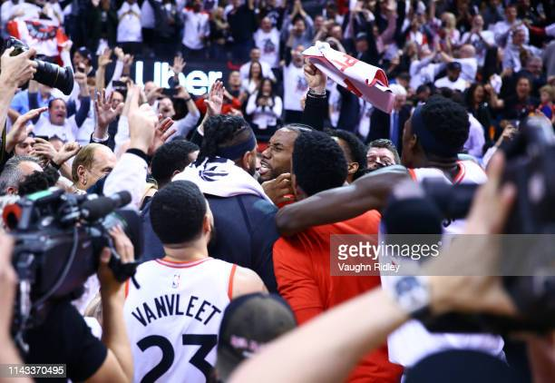 Kawhi Leonard of the Toronto Raptors celebrates with teammates after sinking a buzzer beater to win Game Seven of the second round of the 2019 NBA...