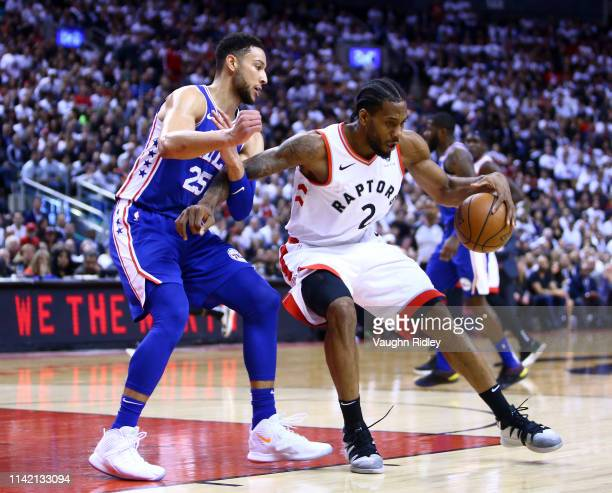 Kawhi Leonard of the Toronto Raptors dribbles the ball as Ben Simmons of the Philadelphia 76ers defends in the second half during Game Five of the...