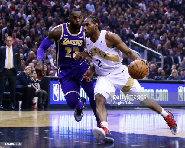 Kawhi Leonard of the Toronto Raptors dribbles the ball as LeBron James of the Los Angeles Lakers defends during the first half of an NBA game at...