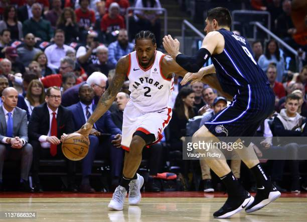 Kawhi Leonard of the Toronto Raptors dribbles the ball as Nikola Vucevic of the Orlando Magic defends during Game Two of the first round of the 2019...