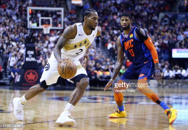 Kawhi Leonard of the Toronto Raptors dribbles the ball as Paul George of the Oklahoma City Thunder defends during the second half of an NBA game at...