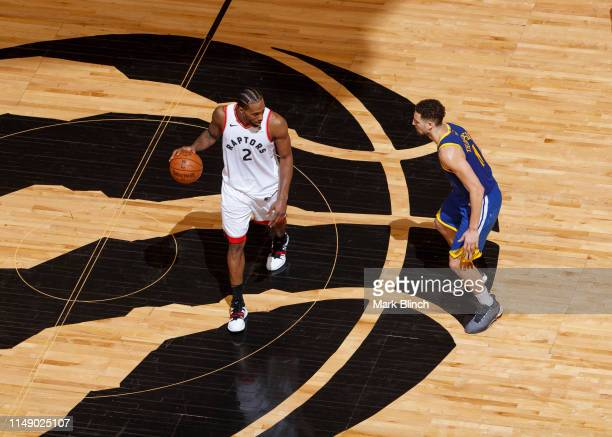 Kawhi Leonard of the Toronto Raptors dribbles the ball at center court while guarded by Klay Thompson of the Golden State Warriors during Game Five...