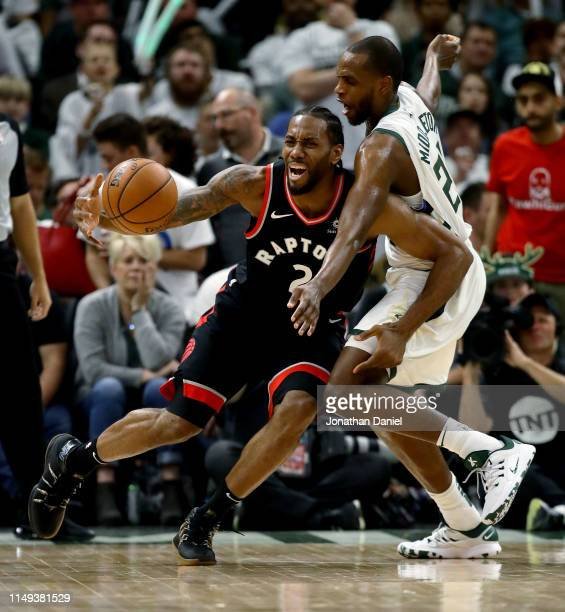 Kawhi Leonard of the Toronto Raptors dribbles the ball while being guarded by Khris Middleton of the Milwaukee Bucks in the third quarter in Game One...