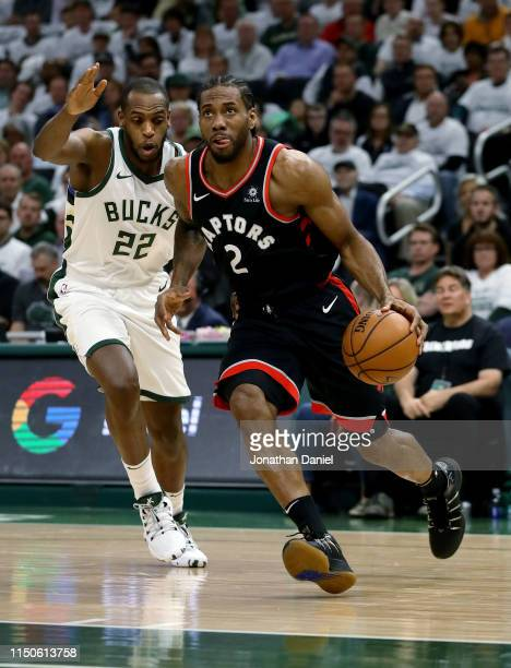 Kawhi Leonard of the Toronto Raptors dribbles the ball while being guarded by Khris Middleton of the Milwaukee Bucks in the first quarter in Game One...