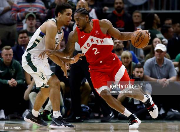Kawhi Leonard of the Toronto Raptors dribbles the ball while being guarded by Malcolm Brogdon of the Milwaukee Bucks in the fourth quarter during...