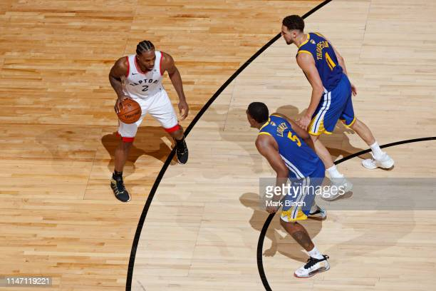 Kawhi Leonard of the Toronto Raptors dribbles the ball while guarded bt Kevon Looney and Klay Thompson of the Golden State Warriors during Game One...