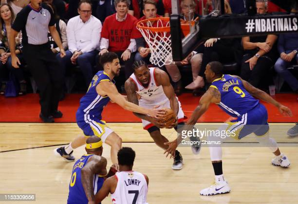 Kawhi Leonard of the Toronto Raptors drives to the basket against Shaun Livingston and Andre Iguodala of the Golden State Warriors in the first half...