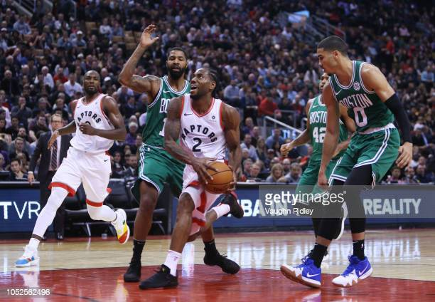 Kawhi Leonard of the Toronto Raptors drives to the basket as Marcus Morris and Jayson Tatum of the Boston Celtics defend during the second half of an...
