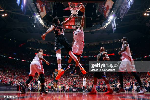 Kawhi Leonard of the Toronto Raptors dunks the ball against Giannis Antetokounmpo of the Milwaukee Bucks during Game Six of the Eastern Conference...