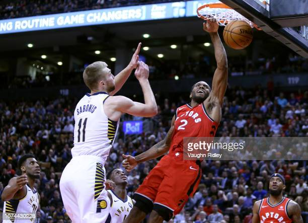 Kawhi Leonard of the Toronto Raptors dunks the ball as Domantas Sabonis of the Indiana Pacers defends during the second half of an NBA game at...