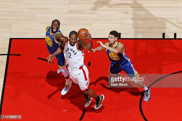 Kawhi Leonard of the Toronto Raptors grabs a rebound against Draymond Green and Klay Thompson of the Golden State Warriors during Game Two of the NBA...