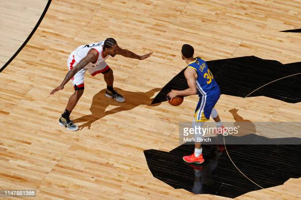 Kawhi Leonard of the Toronto Raptors guards Stephen Curry of the Golden State Warriors at center court during Game Two of the NBA Finals on June 2...