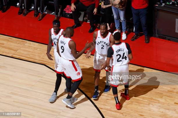 Kawhi Leonard of the Toronto Raptors high fives his teammates during Game Six of the Eastern Conference Finals against the Milwaukee Bucks on May 25...
