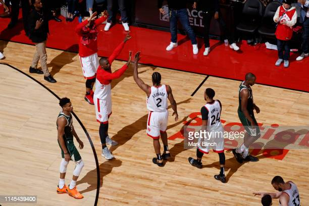 Kawhi Leonard of the Toronto Raptors highfives teammates while walking off court against the Milwaukee Bucks during Game Four of the Eastern...