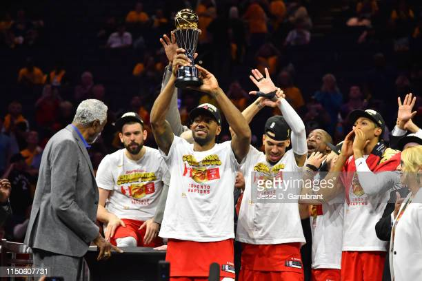 Kawhi Leonard of the Toronto Raptors hoists the Bill Russell MVP Trophy after defeating the Golden State Warriors in Game Six of the NBA Finals on...