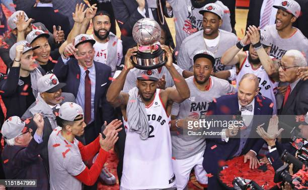 Kawhi Leonard of the Toronto Raptors hoists the Eastern Conference Championship trophy after defeating the Milwaukee Bucks in Game Six of the NBA...
