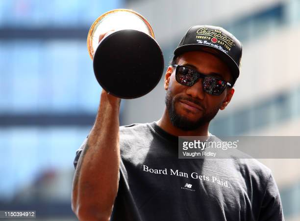 Kawhi Leonard of the Toronto Raptors holds the MVP trophy during the Toronto Raptors Victory Parade on June 17 2019 in Toronto Canada The Toronto...