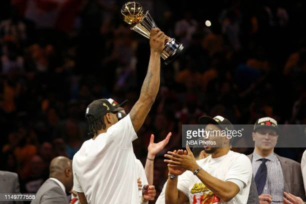 Kawhi Leonard of the Toronto Raptors holds up the Bill Russell Finals MVP Trophy after winning Game Six of the NBA Finals against the Golden State...