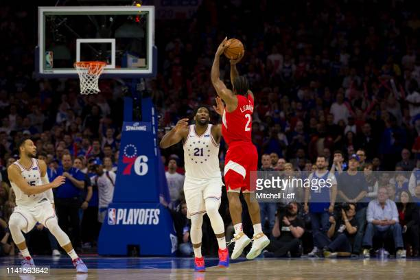 Kawhi Leonard of the Toronto Raptors makes a three point basket against Joel Embiid of the Philadelphia 76ers in the fourth quarter of Game Four of...