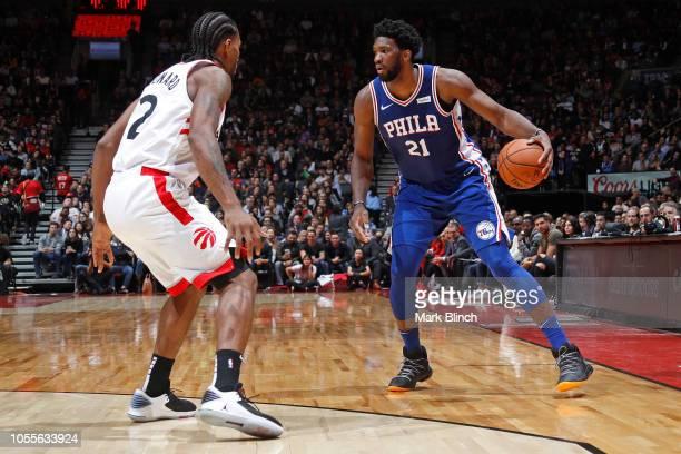 Kawhi Leonard of the Toronto Raptors plays defense against Joel Embiid of the Philadelphia 76ers on October 30 2018 at Soctiabank Arena in Toronto...