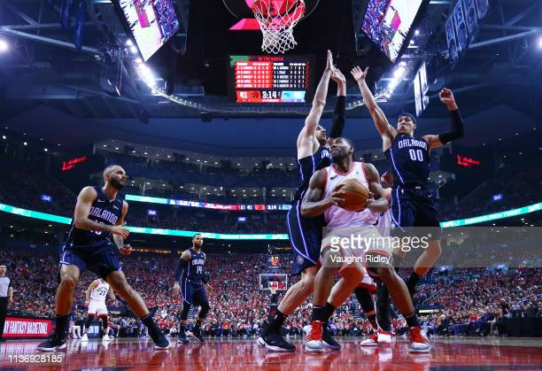Kawhi Leonard of the Toronto Raptors shoots the ball as Nikola Vucevic and Aaron Gordon of the Orlando Magic defend during Game One of the first...