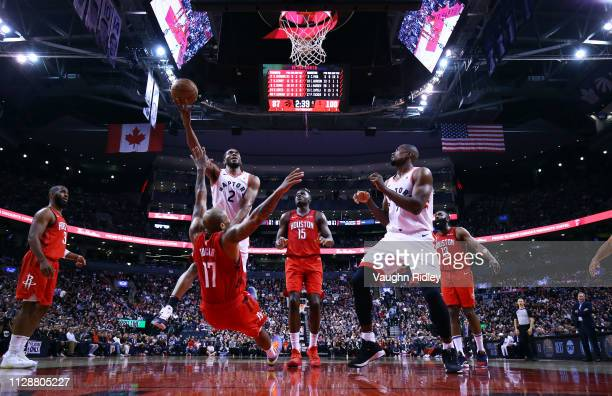 Kawhi Leonard of the Toronto Raptors shoots the ball as PJ Tucker of the Houston Rockets falls to the ground during the second half of an NBA game at...