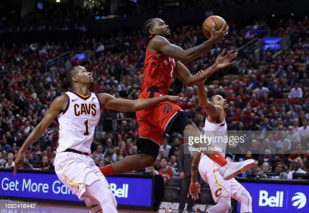 Kawhi Leonard of the Toronto Raptors shoots the ball as Rodney Hood and George Hill of the Cleveland Cavaliers defend during the second half of the...