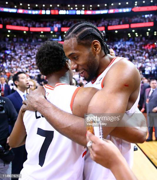 Kawhi Leonard of the Toronto Raptors speaks with Kyle Lowry after sinking a buzzer beater to win Game Seven of the second round of the 2019 NBA...