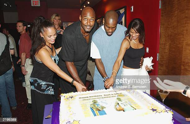 Kay and Karl Malone join Gary and Monique Payton to cut a birthday cake celebrating both Los Angeles Lakers players' birthdays at the Lucky Strike on...