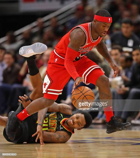 Kay Felder of the Chicago Bulls runs down a loose balll as Kent Bazemore of the Atlanta Hawks hits the floor at the United Center on October 26 2017...