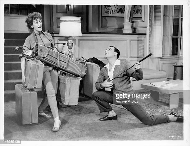Kay Kendall carrying golf bag and luggage as Gene Kelly kneels before her in a scene from the film 'Les Girls' 1957