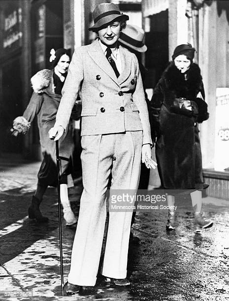 Kay Palmquist models a trousers suit in downtown Minneapolis whil other women stroll by in fur coats