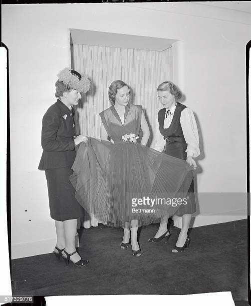 Kay Van Epps fashion editor of the Knickerbocker News Albany New York admires a green nylon garden party gown designed by Pauline Trigere The ankle...