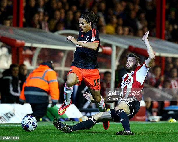 Kay Voser of Fulham looks to get past Brentford's Stuart Dallas during the Capital One Cup Second Round match between Brentford and Fulham at Griffin...