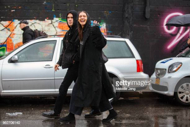 Kaya Wilkins and Aaron Maine exit the Eckhaus Latta show in Brooklyn in all black and hoods on February 10 2018 in New York City