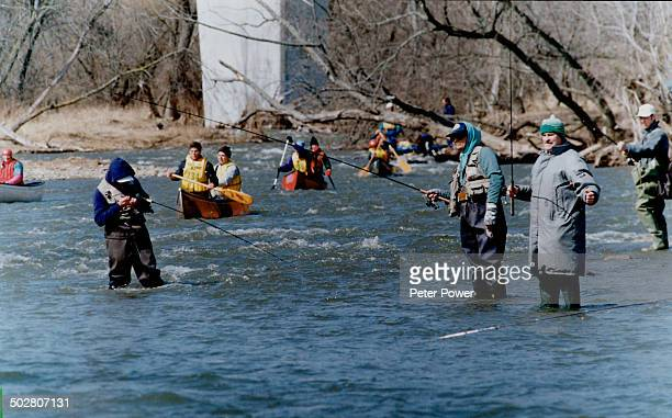Kayak and canoe racers test their skills on a slalom course set up on the Credit River in Mississauga yesterday as fishermen try their luck on the...