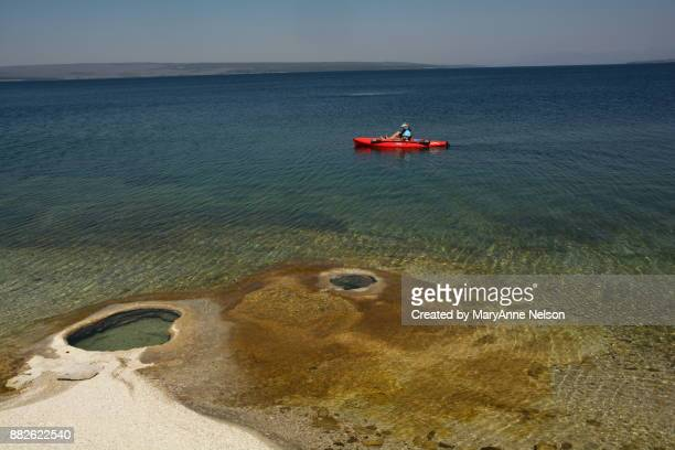 kayak going by geyser in yellowstone lake - mary lake stock photos and pictures