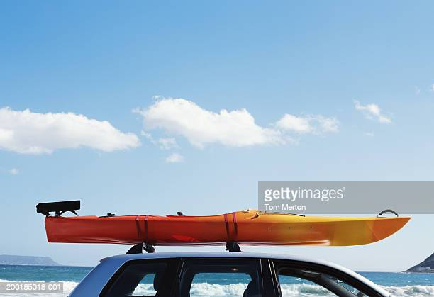 Kayak mounted on roof of car, sea in background