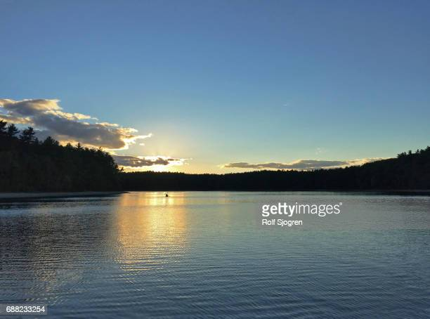kayak paddlers on walden pond at sunset - walden pond stock pictures, royalty-free photos & images
