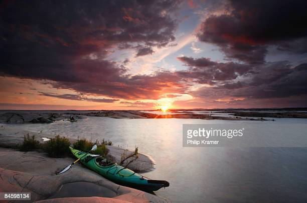 kayak rests on rocks at sunset. - moored stock pictures, royalty-free photos & images