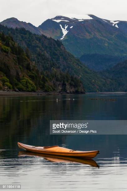 a kayak sits on the tranquil water with a view of forests and a mountain range in the background, kachemak bay state park - kachemak bay stock pictures, royalty-free photos & images