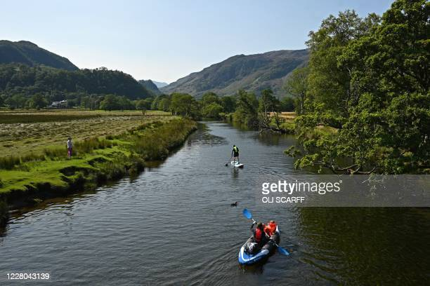 Kayaker and a paddleboarder in the River Derwent in the Lake District in north west England on August 14 as many people take advantage of the...