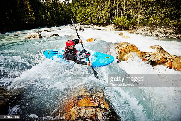 Kayaker entering white water rapids