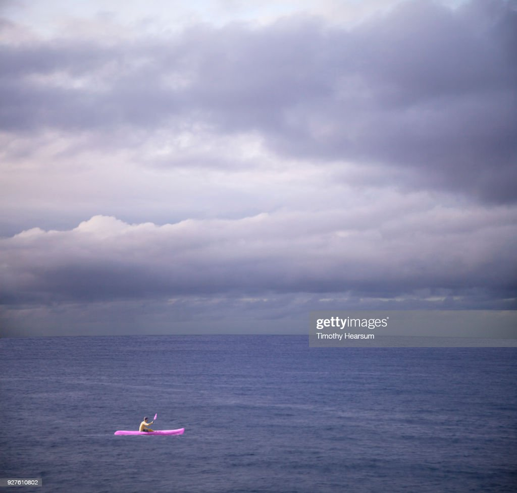Kayaker in bright ultraviolet vessel paddling in an ultraviolet sea with ultraviolet clouds beyond : Stock Photo