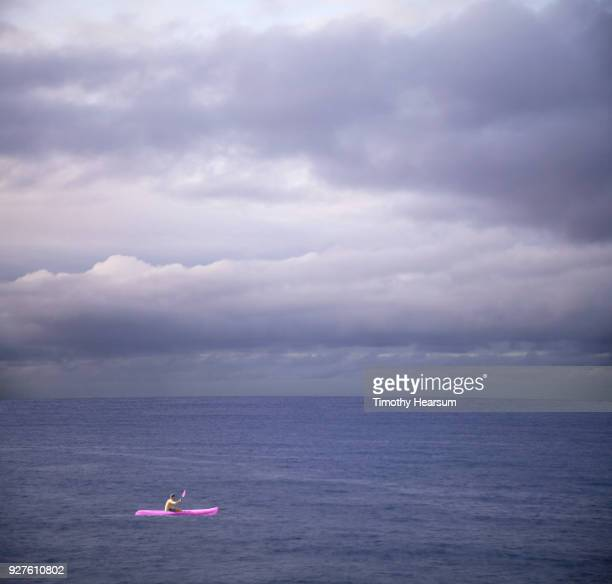 Kayaker in bright ultraviolet vessel paddling in an ultraviolet sea with ultraviolet clouds beyond