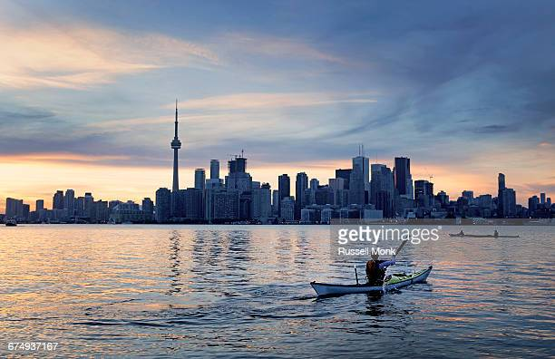 a kayaker in front of a city skyline - toronto stock pictures, royalty-free photos & images