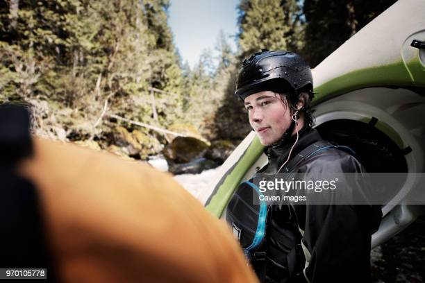 kayaker looking at friend while standing in forest - ウオータースポーツ ヘルメット ストックフォトと画像