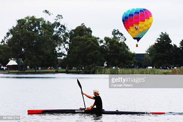 A kayaker paddles pass a hot air balloon as it rises over Innes Common Park during the Balloons over Waikato Festival on March 27 2015 in Hamilton...