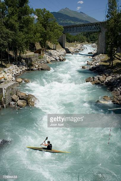 Kayaker practices on the whitewater slalom course. France.