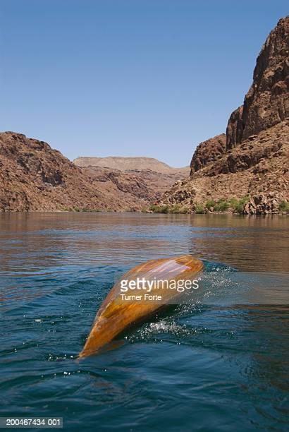 Kayaker rolling wooden kayak in river